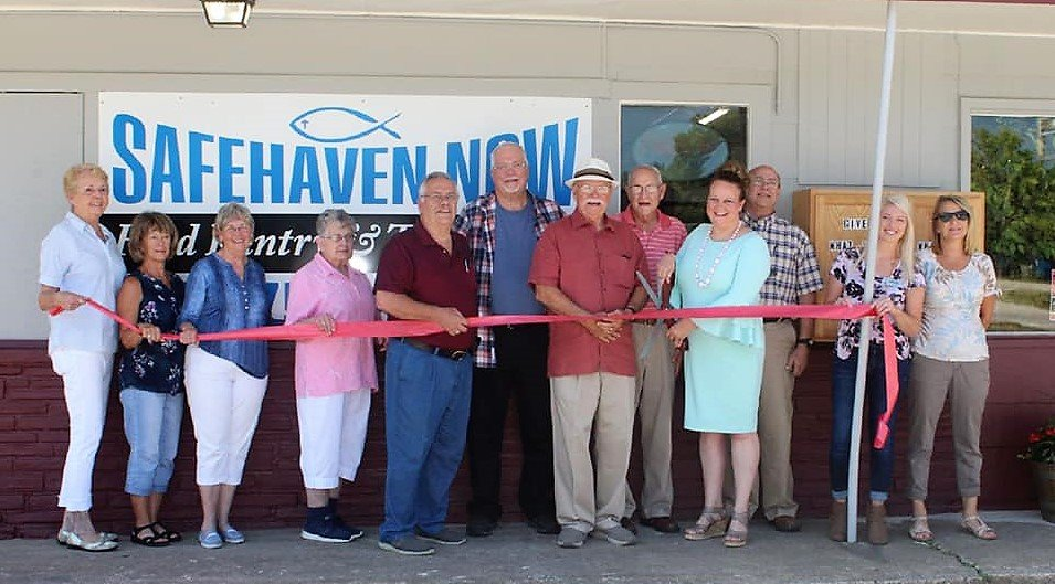 Volunteers cutting the grand opening ribbon in front of the new rogersville location